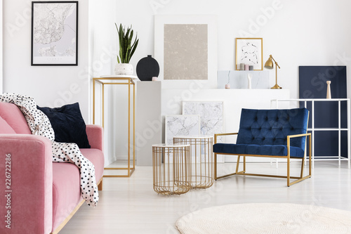 Silver abstract painting on the wall of trendy living room with two elegant coffee tables, petrol blue armchair and powder pink couch with doted blanket on it - 226722286