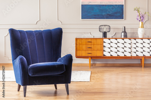 Close-up of a dark blue armchair with a vintage cabinet in the background in a living room interior © Photographee.eu