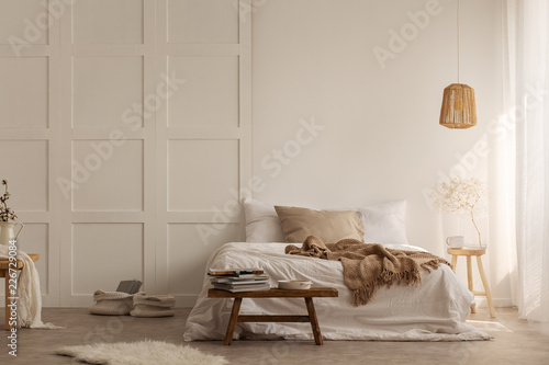 Leinwandbild Motiv Natural blanket on white bed in simple bedroom interior with fur next to wooden stool. Real photo