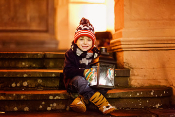 Little cute kid boy with with a light lantern on stairs near church.