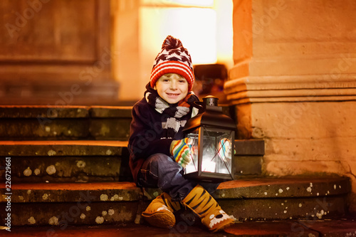 Leinwandbild Motiv Little cute kid boy with with a light lantern on stairs near church.