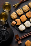 Mochi assortment with chopticks and tea traditional japanese rice dessert top view