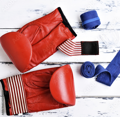 pair of leather red boxing gloves, blue bandage