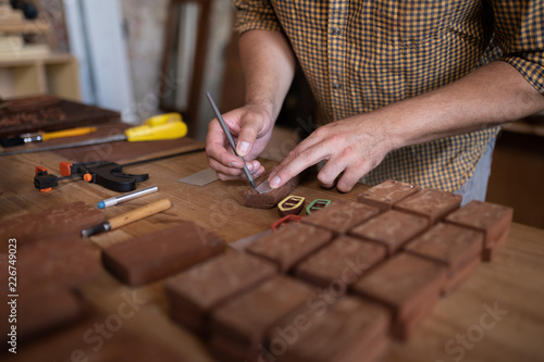 A joiner's table. Close-up view of joiner's hands while he holds a pencil and works with wood. - 226749023
