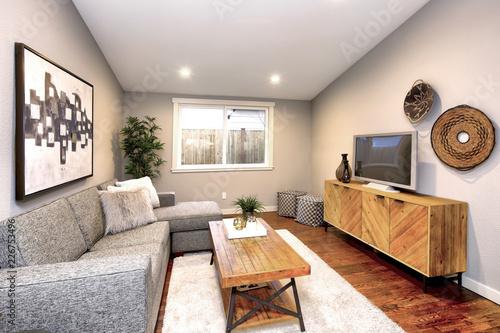 Pokój dzienny w neutralnych kolorach z drewnianą podłogą.