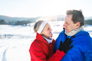 Senior couple runners standing in winter nature, resting.
