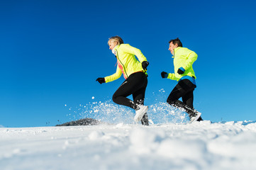 Senior couple runners running in winter nature. Copy space.