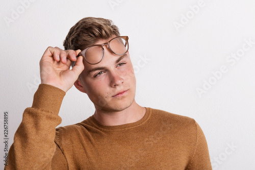 Leinwanddruck Bild A confident young man in a studio, holding glasses on his forehead.