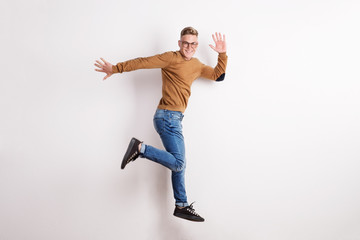Portrait of a happy young man in a studio, jumping.