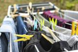 Wäsche hängt über Wäscheständer von bunten Wäscheklammern gehalten, um zu trocknen