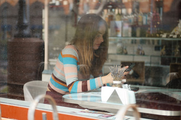 Photo through the window of cute girl with long hair sitting in cafe and chatting on mobile phone