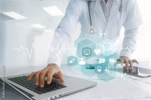 Medicine doctor touching laptop and tablet computer interface as medical network connection with icon modern on virtual screen, Digital healthcare, medical technology network and innovation concept © ipopba