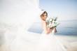 Leinwandbild Motiv Lovely bride in white wedding dress posing near the sea with beautiful background