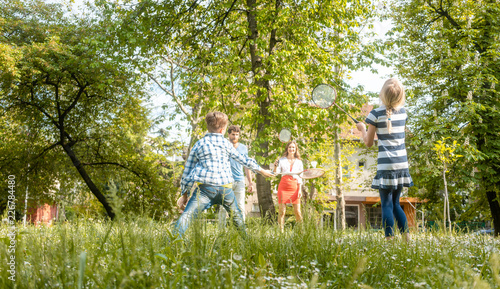 Foto Murales Family playing badminton on a meadow in summer having fun enjoying themselves