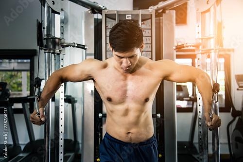Sportowiec kulturysta mięśni trening na symulatorze w siłowni, silny mężczyzna.