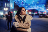 Cute young girl in winter coat standing in street and enjoying beautiful winter evening in decorated streets. - 226787433