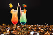 sweet cocktails with straws on golden confetti with copy space