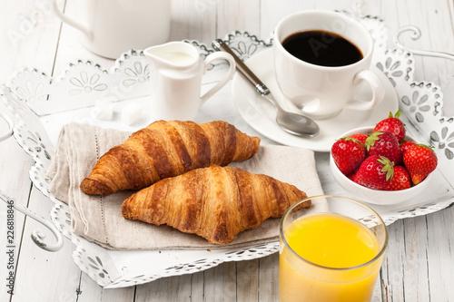 Wall mural Breakfast with croissants, black coffee, orange juice and strawberries