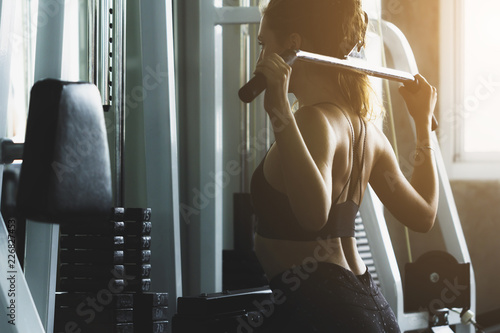 Sticker Closed up young woman working out in modern gym, with sun flare effect reflects on equipment.