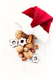 Santa Claus hat with nuts, spices and chocolates. Christmas background. White wooden background. Top view. Copy space.  - 226829477