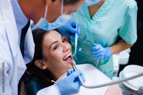 Her new dentist is not scary at all! Top view of dentist with his assistant examining his beautiful patient in dentist's office - 226837838