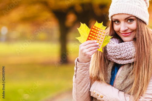 Foto Murales Woman in autumn park holding vitamins medicines