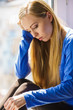 Leinwandbild Motiv Sad depressed teen girl sitting on window sill
