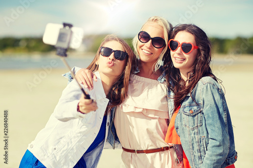 Leinwandbild Motiv summer vacation, holidays, travel, technology and people concept- group of smiling young women taking picture with smartphone on selfie stick on beach