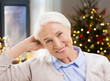 holidays, age and people concept - happy smiling senior woman at home over christmas tree lights background