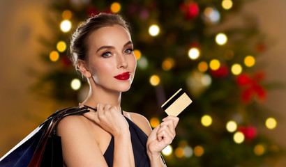 luxury, holidays and saleconcept - beautiful woman with credit card and shopping bags over christmas tree lights background