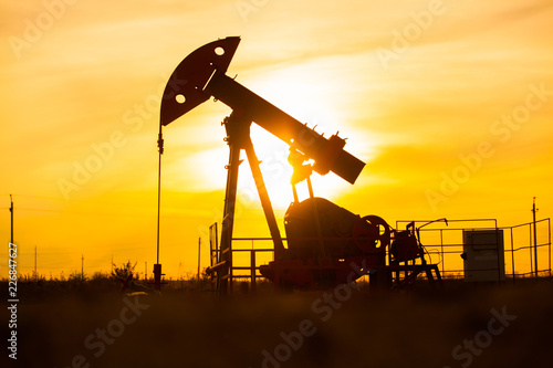 In the evening, the outline of the oil pump. The oil pump, industrial equipment. Oil field site, oil pumps are running. Rocking machines for oil production in a private sector.