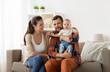 Quadro family, parenthood and people concept - happy mother, father with baby at home