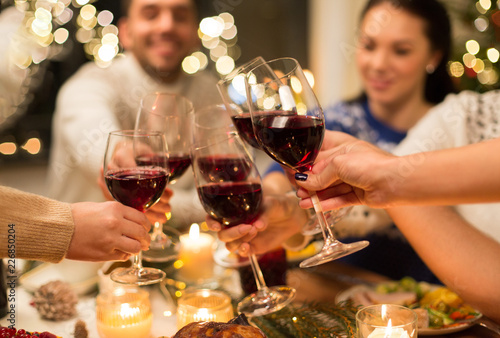 Leinwanddruck Bild holidays and celebration concept - close up of happy friends having christmas dinner at home, drinking red wine and clinking glasses