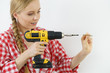 Quadro Woman drilling in wall