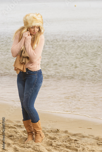 Foto Murales Woman in stylish outfit feeling cold by the sea