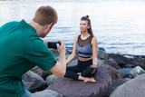 Man photographs meditating woman with cameraphone