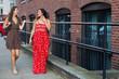 Two female friends walking and talking outside on sidewalk