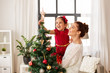 Quadro family, winter holidays and people concept - happy mother and little daughter decorating christmas tree at home