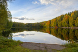 The most beautiful scenery on an autumn evening. Colorful forest and reflective water. Wallpaper with blue sky and reflection in the water. - 226862403
