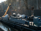 Construction barge with a crane, inflatable boat, bags, mechanisms on the river in the summer on a sunny day - 226871865