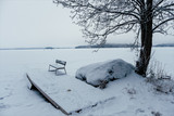 Bench at the edge of the frozen lake - 226878246