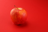 Ripe red apple with leaves on red background.