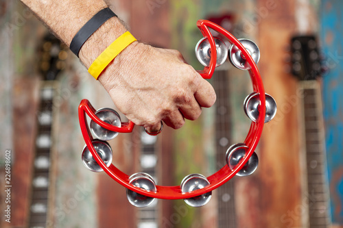 Mans hand holding a tambourine with guitars in the background - 226898602