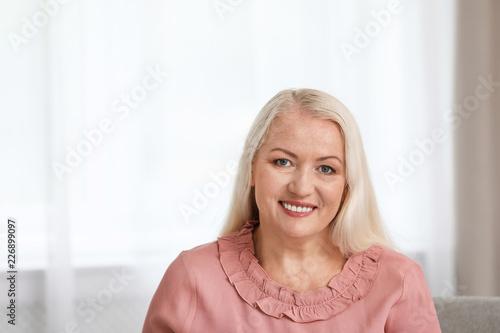 Leinwandbild Motiv Portrait of beautiful older woman against blurred background