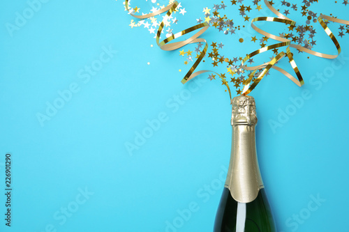 Leinwanddruck Bild Creative flat lay composition with bottle of champagne and space for text on color background