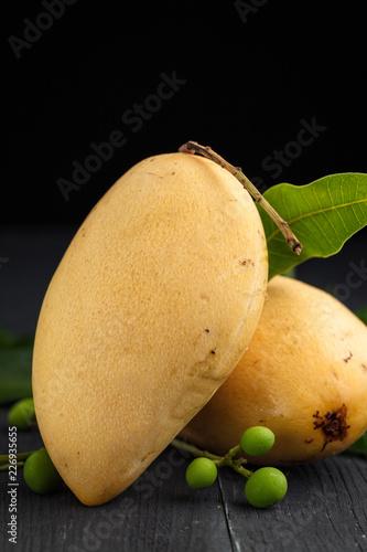 Foto Murales Ripe yellow Mango on wooden dark background.