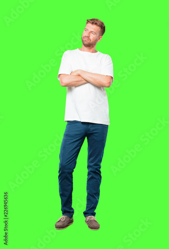 """Leinwanddruck Bild young blonde man with a proud, happy and confident expression; accepting a challenge with arms crossed, smiling and sure of success, giving an """"achiever"""" look."""