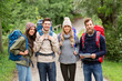travel, tourism, hiking and people concept - happy friends or travelers with backpacks and map on road in woods