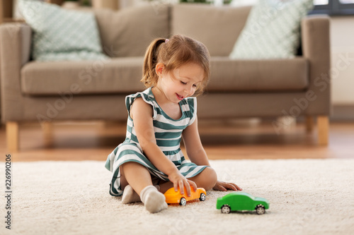 Foto Murales childhood and people concept - happy three years old baby girl playing with toy car at home