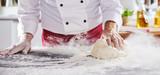 Man sliding dough along table to pick up flour - 226990471